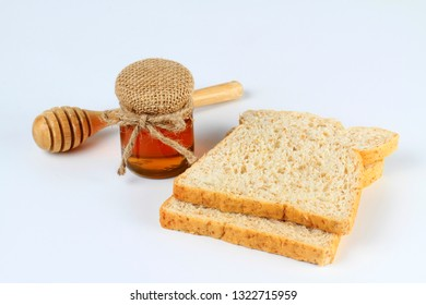 Whole wheat bread and honey on white background