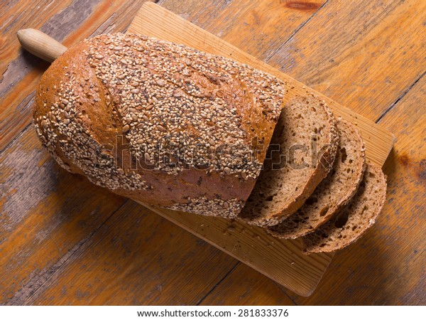 Whole wheat bread with seeds on a cutting board.