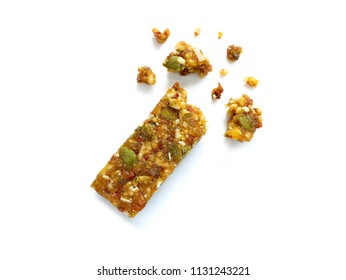 Whole wheat cereal bar or flapjack with pumpkin seeds and dried fruit with crumbs isolated on white background. Top view.