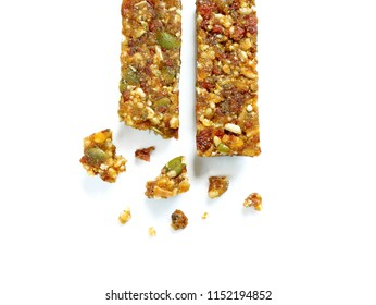 Whole wheat cereal bars or flapjacks with pumpkin seeds and dried fruit with crumbs isolated on white background. Top view.