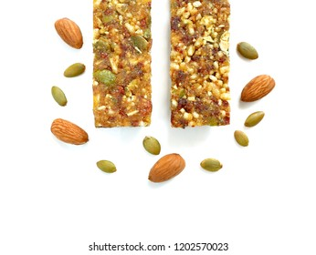 Whole wheat cereal bars or flapjacks with pumpkin seeds, almonds and dried fruit isolated on white background. Top view.
