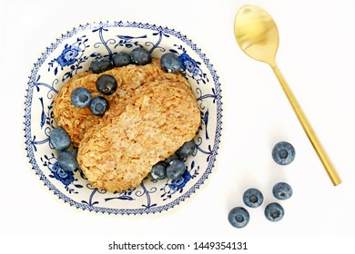 Whole wheat cereal biscuit with fresh organic blueberries and milk on white background.  Healthy breakfast concept. Horizontal in flat lay composition.