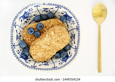 Whole wheat cereal biscuit with fresh organic blueberries on white background.  Healthy breakfast concept. Horizontal in flat lay composition.