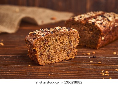 Whole wheat craft bread on wooden background. The concept of healthy food and traditional bakery. Rustic