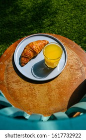 Whole wheat croissant and pineapple juice on the table.