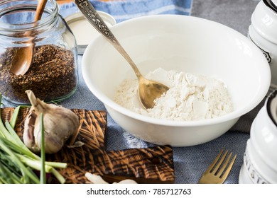 Whole wheat flour mixed with spices, herbs, greens in white bowl on fabric background in kitchen