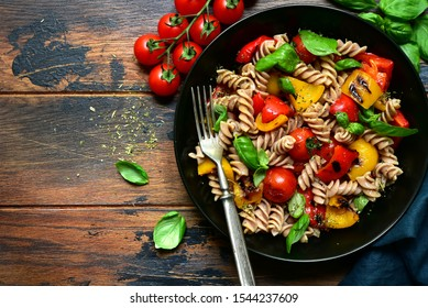 Whole wheat fusilli pasta with grilled vegetables in a black bowl on a wooden background. Top view with copy space.