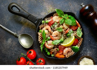 Whole wheat fusilli pasta with shrimps and vegetables in a skillet on a dark slate, stone, concrete or metal background.Top view.