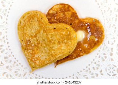 Whole wheat heart shaped pancakes with butter, syrup and sprinkled sugar for a special Valentine's Day breakfast.