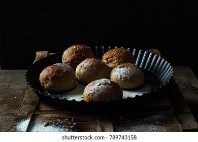 Whole wheat kaiser rolls with sesame seeds on retro crate in black pan