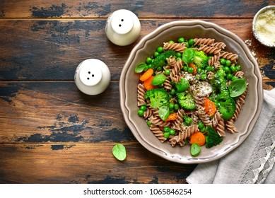 Whole wheat pasta primavera in a rustic bowl on an old wooden background.Top view with copy space.