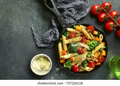 Whole wheat pasta with vegetables in a skillet over dark green slate,stone or concrete background.Top view with space for text.