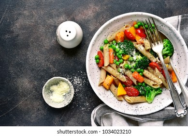 Whole wheat penne pasta with vegetables in a white bowl over dark slate, stone or metal background.Top view.