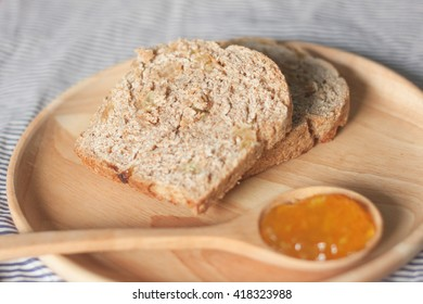 whole wheat resin bread served with orange jam in wooden set