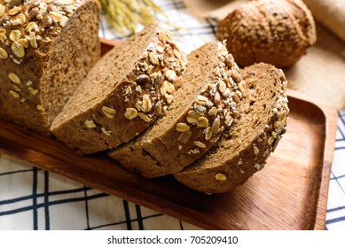 Whole Wheat Rye Bread Loaf is cut and placed on a wooden plate.And put on a tablecloth.