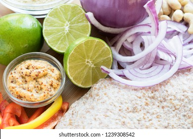 Whole wheat tortillas and fresh lime, peppers and onion for Mexican cooking.