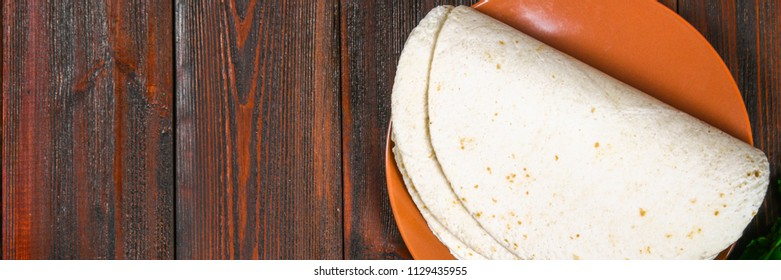 whole wheat tortillas on wooden board and vegetables.