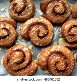Whole wheat vegan cinnamon rolls drizzled with glaze, baked with 100% whole grain flour, temptingly patterned on a sheet pan.