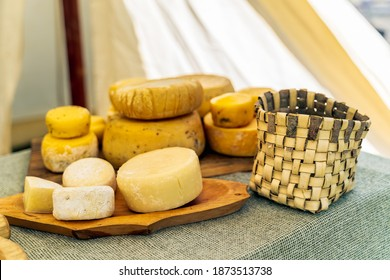 Whole wheels of yellow cheese, homemade on table display at historical reenactment of Slavic or Vikings lifestyle around 11th century, Cedynia, Poland