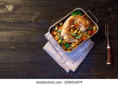 Whole wild backed rabbit with vegetables, spices and herbs,oregano, mint in metallic dish on old black rustic wooden background. Clean eating, haelthy food and AIP, Paleo  diet concept. Top view,