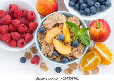 whole-grain flakes with fresh fruit and berries, close-up, top view, horizontal