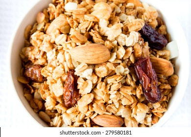 Wholegrain muesli (granola) close up texture with raisin, dry fruits, nuts and cereals. Healthy food.