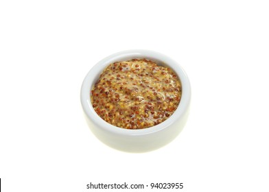 Wholegrain mustard in a ramekin isolated against white
