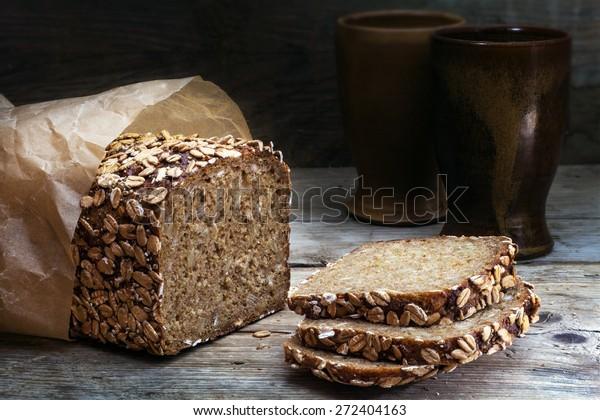 VollkornRoggenbrot mit Samen auf verwittertem Holzbrett, rustikales Erdgeschirr auf dunklem Hintergrund