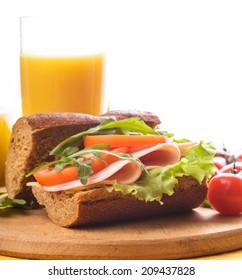 Wholegrain sandwich with ham, tomato, lattuce and arugula with glass of orange juice. Breakfast