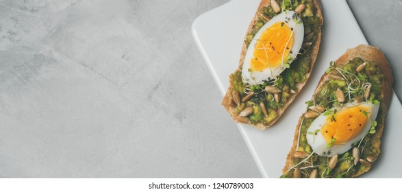 Whole-grain toasts plated avocado with eggs, mini herbs, sunflower seeds served on a ceramic white board over grey concrete background, top view, long wide banner background. Diet food concept.