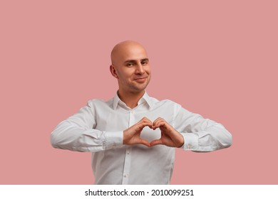 Wholeheartedly. Happy bald man with bristle in white shirt, holds fingers in heart gesture. Shows his love and pure intentions. Assures that he can be trusted. Isolated over pink background