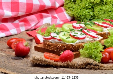 Wholemeal grain bread with curd cheese, fresh radish, cucumber and tomatoes on a wooden cutting board - concept of healthy fitness breakfast or snack, fresh salad in the background