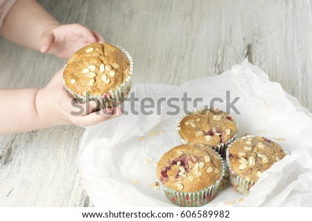 Wholemeal raspberry muffins with banana and oats in child's hands