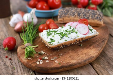 wholemeal roll with quark and fresh chives, radish and tomatoes on a rustic wooden table - healthy breakfast with fresh herbs