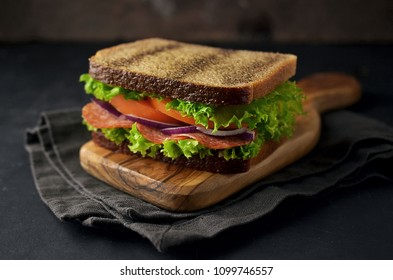 Wholemeal sandwich with vegetables on cutting board