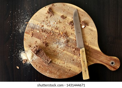 Wholemeal and white breadcrumbs and bread leftovers on the rounded wooden cutting board on dark brown tabletop with rustic knife. Top view from above, copy space