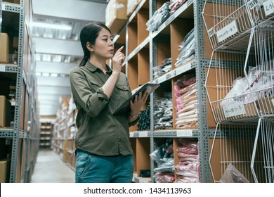 wholesale logistic people and export concept. female supervisor with mobile pad at warehouse doing stock taking. elegant young girl storehouse staff counting by digital tablet in stockroom indoors.