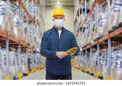卸売り、ロジスティック、人、輸出のコンセプト – 倉庫の背景に顔を保護する医療マスクを着けた安全なヘルメットをかぶった男性の労働者