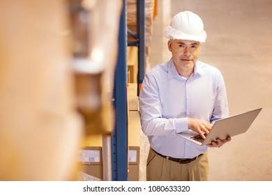 Wholesale production. Positive joyful businessman having a warehouse while dealing with wholesale production