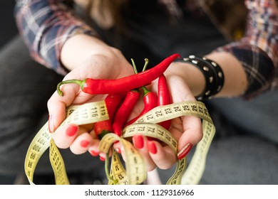 wholesome balanced nutrition for weightloss and fitness. organic natural products for dieting. woman holding fresh chili pepper with twisted measuring tape in hand.