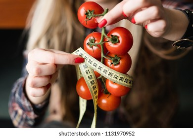 wholesome balanced nutrition for weightloss and fitness. organic natural products for dieting. woman holding fresh tomatoes with twisted measuring tape in hand.