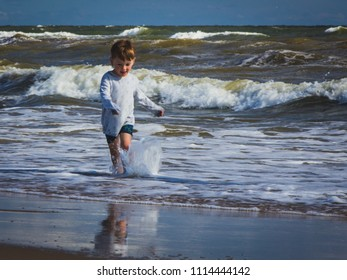 Wholesome kid with wet clothes runs on the beach in seawater.