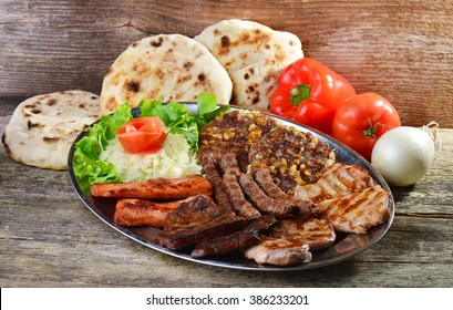 Wholesome platter of mixed meats including grilled steak. Balkan food