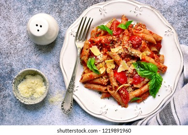 Wholewheat penne pasta with bolognese sauce on a white plate ove grey slate, stone or concrete background.Top view with copy space.