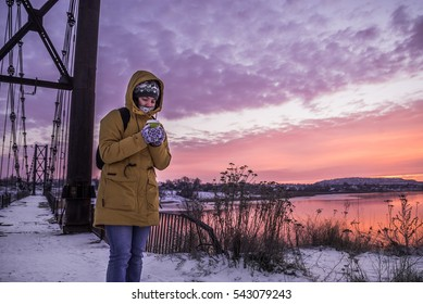whoman trying to worm up with coffie on sunrise in cold day