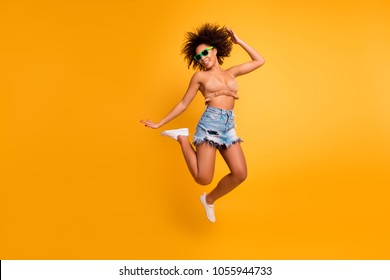 Whoo! I go crazy! Dreams come true! Full-length full-size photo of cheerful cute relaxed full of energy positive afro woman with curly short brown hair casual clothed, isolated on yellow background