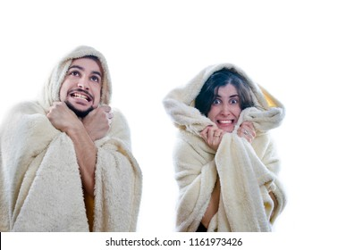 whopping couple isolated on white poses for photo depicting the cold while they are covered with a quilt