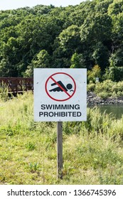 A whte sign with a no swimming icon and says swimming is prohibited is posted at Sunken Meadow State Park with a bridge and trees in the background.