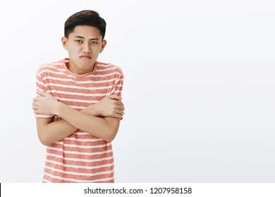 Why so cold like in fridge. Displeased intense asian teenage guy in striped t-shirt trembling hugging himself with hands crossed against chest, pursing lips, have not prepared to chilly windy weather
