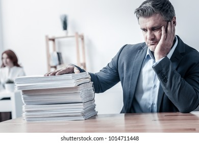 Why did this happen to me. Poor mature man resting his head on a hand while sitting at a table and looking at a pile of different business documents with eyes full of sadness.
